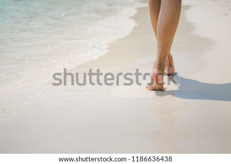 Closeup travel woman foot of walking on beach with sea wave in summer, holidays background, vacation concept #1186636438