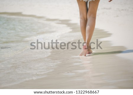 Closeup travel woman foot of walking on beach with sea wave in summer, holidays background, vacation concept #1322968667