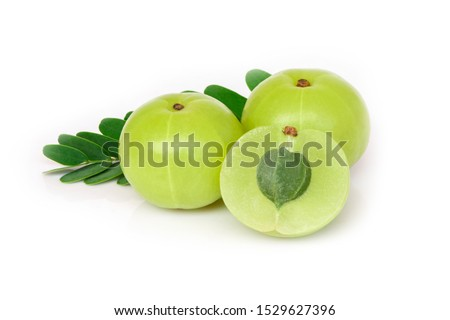 Closeup two Indian gooseberry fruits or Amla berry ( phyllanthus emblica ) with green leaf and sliced isolated on white background.  Stock photo ©