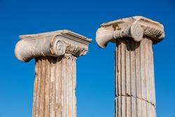 Closeup two white roman pillar tops, acropolis greece, delos island acropolis, blue skies background