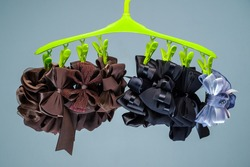 Closeup various styles of elegant hair bows hanged in clothespins of the hanger, designed hair bow in brown, black, and silver-blue color