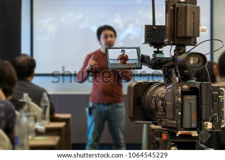 Closeup Video recording the Asian Speaker with casual suit on the stage over the presentation screen in the meeting room of business or education seminar, event and seminar concept #1064545229