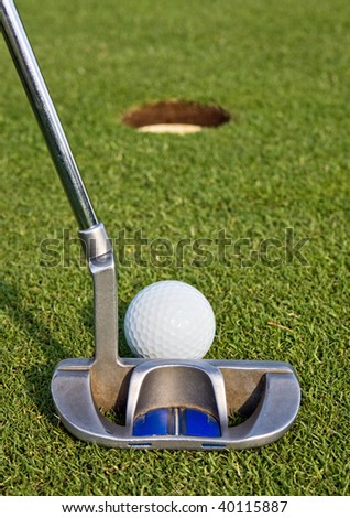 Closeup view from behind a putt on a golf green, as the golfer lines up a short putt. Short depth of field with focus on the golf ball. - stock photo
