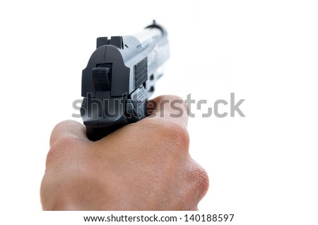 Closeup view from behind of a male hand holding a pistol taking aim away from the camera with shallow depth of field on a white background