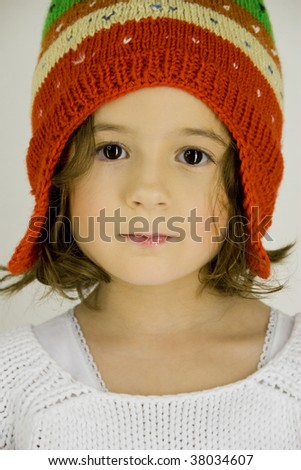 closeup view of a beautiful little girl with big brown eyes and knitting cap