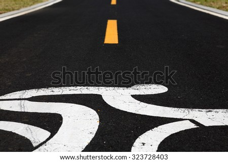 Closeup view of a bicylist symbol on a tarmac road.