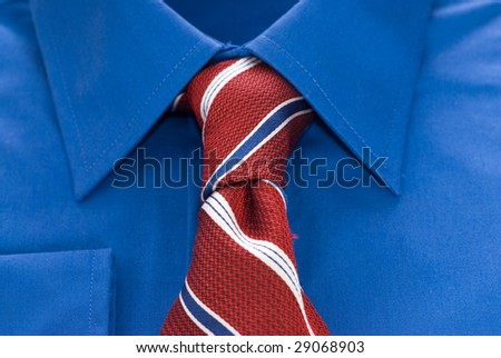 Closeup view of a blue shirt and a striped tie