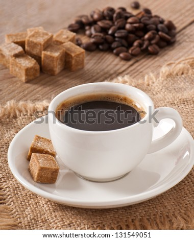 closeup view of a cup of coffee, brown sugar and coffee beans