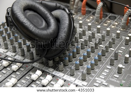 closeup view of a DJ's mixing desk with a pair of headphones
