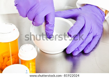 Closeup view of a pharmacist's hands, using a mortar and pestle.