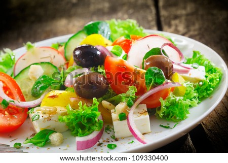Closeup view of a plate of fresh healthy Greek salad with lettuce, basil, feta, onion, olives, radish and tomato