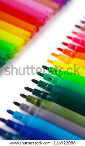 Closeup view of a row of colorful felt tip pens over white background - stock photo