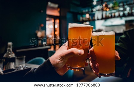 Closeup view of a two glass of beer in hand. Beer glasses clinking in bar or pub Stok fotoğraf ©