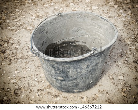 Closeup view of a used masonry bucket on a concrete floor.
