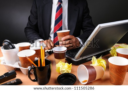 Closeup view of a very cluttered and overworked businessman's desk. Man is holding a coffee cup and crumpled papers litter his workspace. Horizontal format on a light to dark gray background.