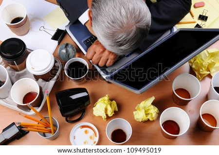 Closeup view of a very cluttered businessman's desk. Overhead view with man's head on laptop keyboard and scattered coffee cups and office supplies. Horizontal format. - stock photo