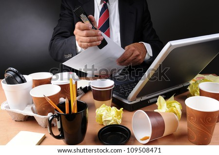Closeup view of a very cluttered businessmans desk. Man is stapling papers with coffee cups and crumpled papers litter his workspace. Horizontal format on a light to dark gray background.
