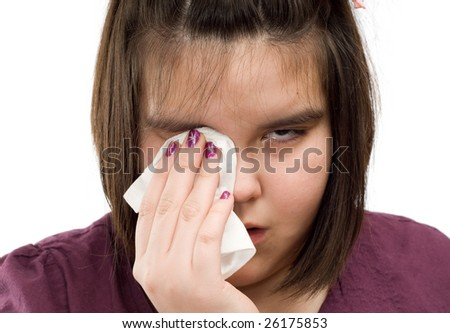 Closeup view of a young girl wiping tears from her eyes with a tissue