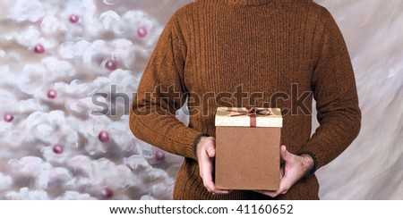 Closeup view of a young man wearing a sweater and holding a holiday gift