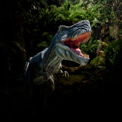 Closeup view of an angry T-Rex dinosaur figurine in jungle. Monstrous animal with open mouth and sharp teeth