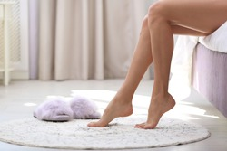 Closeup view of barefoot woman sitting on bed. Floor heating