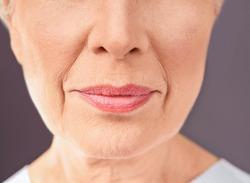 Closeup view of beautiful elderly woman on gray background