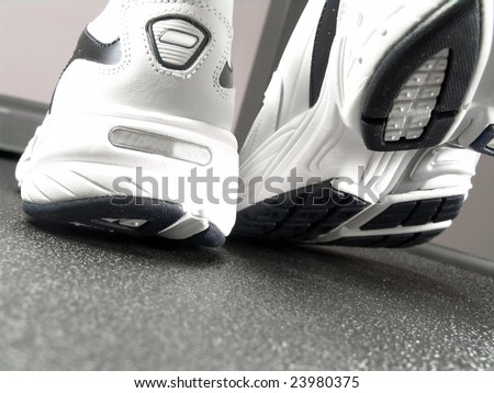Closeup view of brand new sport shoes running walking on a treadmill (low angle perspective)