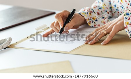 Closeup view of businesswoman proofreading a contract following lines with a pen.