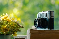 Closeup view of countryside windowsill and sunny green blurry foliage of spring or summer trees behind glass of window. Several old books, vintage photocamera, bouquet of flowers in metal enamel mug