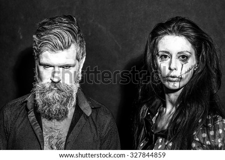 Closeup view of couple of painted halloween holy chracters woman and man with long lush beard looking forward on studio wall background black and white, horizontal picture