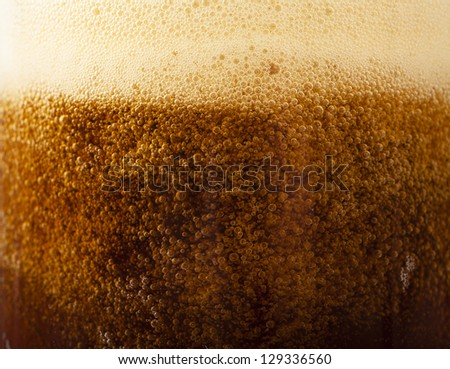Closeup view of dark beer pouring into the glass