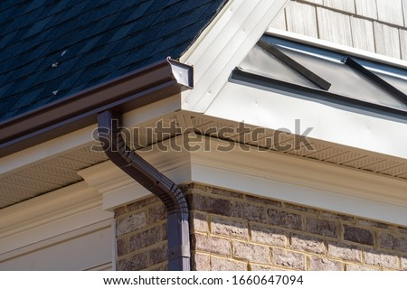 Closeup view of dark brown gutter system with white soffit vent, gutter guard, drop outlet, downspout, vinyl elbows, decorative trim molding, on the corner of a brick luxury house in America Stock photo ©