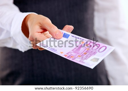 Closeup view of female hand holding five hundred euro banknote. Shallow depth of field.