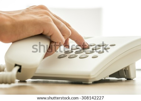 Closeup view of female secretary dialing a telephone number on white landline phone. Conceptual for global communication, technical support and customer service.