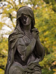 Closeup view of female statue woman sculpture folding hands prayer mourning grief graveyard tombstone Pere Lachaise cemetery Paris France Europe