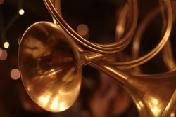 Closeup view of few shiny yellow golden wing musical instrument of horn as christmas little toys, horizontal picture