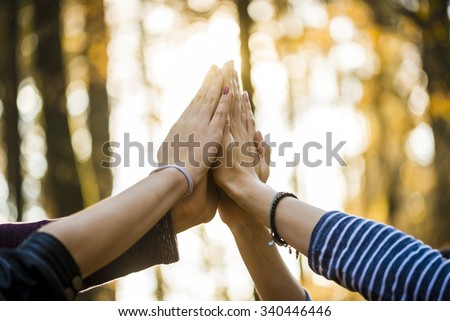 Closeup view of four people joining their hands together high up in the air outside in a forested area.
