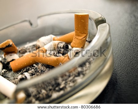 Closeup view of full ashtray on the table.