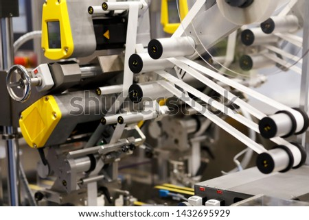 Closeup view of industrial automatic self adhesive labeling machine. Selective focus.