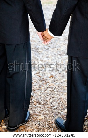 Closeup view of interracial gay couple getting married in tuxedos and holding hands.  Wedding band is visible.