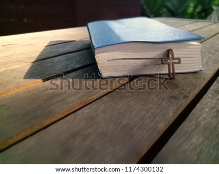 Closeup view of Jesus christian cross and old book on wood table, God concept picture with selective focus