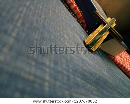 Closeup view of Jesus christian cross leaning against blue covered book of bible, God loving concept picture with selective focus