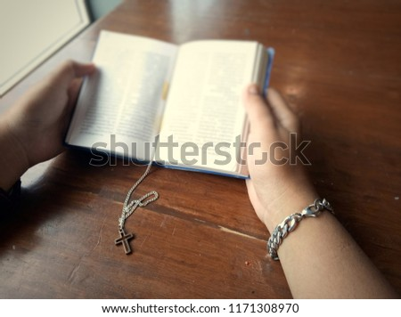 Closeup view of Jesus christian cross necklace and blurred person hand holding old book for reading, God loving concept picture with selective focus process