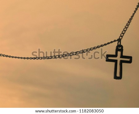 Closeup view of Jesus christian cross necklace hanging on sunset sky background, God loving concept picture with selective focus