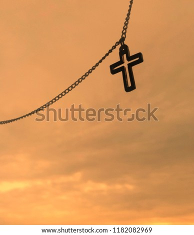 Closeup view of Jesus christian cross necklace hanging on sunset sky, God loving concept picture with selective focus