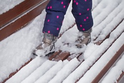 Closeup view of little legs of small baby girl playing in fresh white snow outdoor standing at wooden brown bench covered with snow. Happy wintertime season concept. Horizontal color photography.