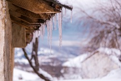 Closeup view of long sharp icicles hanging down from roof of house on sunny frosty cold winter day.