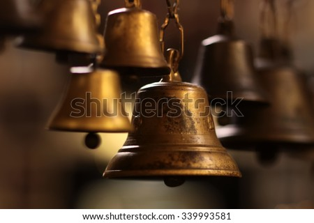 Closeup view of many beautiful old fashioned golden christmas bells hanging as new year toys, horizontal picture