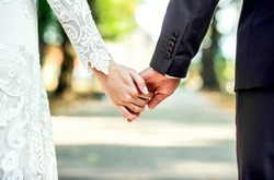 Closeup view of married couple holding hands