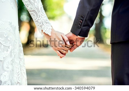 Closeup view of married couple holding hands  #340594079